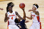 Oral Roberts guard Max Abmas (3) shoots between Florida forward Anthony Duruji (4) and guard Tre Mann (1) during the second half of a college basketball game in the second round of the NCAA tournament at Indiana Farmers Coliseum, Sunday, March 21, 2021 in Indianapolis. (AP Photo/AJ Mast)