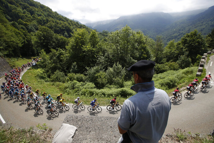 A spectator watches the pack as he rides during the fourteenth stage of the Tour de France cycling race over 117,5 kilometers (73 miles) with start in Tarbes and finish at the Tourmalet pass, France, Saturday, July 20, 2019. (AP Photo/ Christophe Ena)