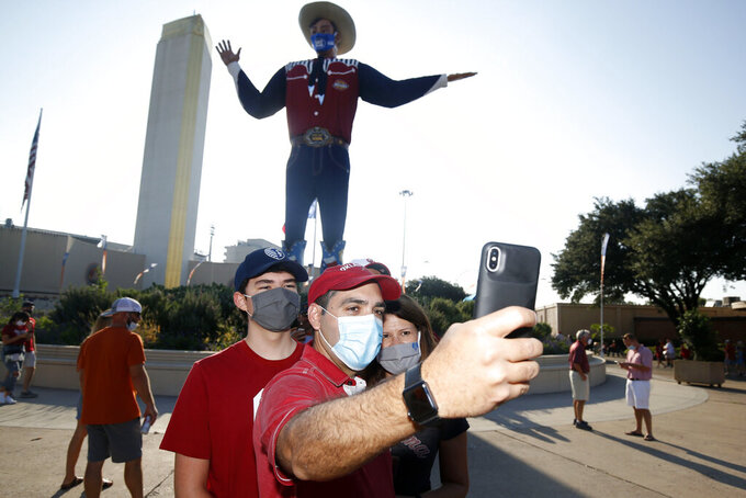 "Oklahoma fans Lucas Aleman, Josias Aleman and Annie Aleman, of Kansas City, take a selfie in front of ""Big Tex"" prior to an NCAA college football game between University of Texas and Oklahoma. in Dallas,  Saturday, Oct. 10, 2020. (AP Photo/Michael Ainsworth)"