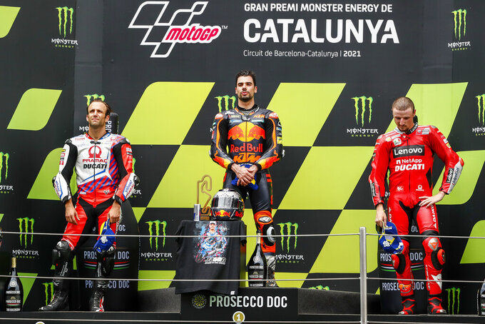 KTM Portuguese rider Miguel Oliveira, center, celebrates from the podium with second placed Ducati-Pramac French rider Johann Zarco, left, and third placed Ducati Australian rider Jack Miller during the Catalunya Motorcycle Grand Prix at the Barcelona Catalunya racetrack in Montmelo, near Barcelona, Spain, Sunday, June 6, 2021. (AP Photo/Joan Monfort)