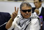 FILE - In this June 12, 2019 file photo, former FARC rebel Seuxis Hernandez, also known as Jesus Santrich, flashes a victory sign at journalists as he attends a session of the Chamber of Representatives at the Colombian congress in Bogota, Colombia. Hernandez along with a group of former peace negotiators for the Revolutionary Armed Forces of Colombia announced in a video published Thursday, Aug. 29, 2019, that they are taking up arms again following what they considered the failure of conservative President Ivan Duque to guarantee their political rights after the signing of a landmark peace deal. (AP Photo/Fernando Vergara, File)
