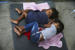 FILE - In this July 17, 2019, file photo, migrant children sleep on a mattress on the floor of the AMAR migrant shelter in Nuevo Laredo, Mexico. A federal judge rules that the Trump administration is operating within its authority when separating families stopped at the Mexican border, rejecting arguments that it was quietly returning to widespread practices that drew international condemnation. (AP Photo/Marco Ugarte, File)