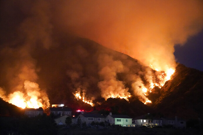 The Ranch Fire burns over a residential area, Thursday, Aug. 13, 2020, in Azusa, Calif. Heat wave conditions were making difficult work for fire crews battling brush fires and wildfires across Southern California. (AP Photo/Marcio Jose Sanchez)