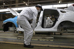 In this April 8, 2020, photo, employees work on a car assembly line at the Dongfeng Honda Automobile Co., Ltd factory in Wuhan in central China's Hubei province. The United States, Japan and France are prodding their companies to rely less on China to make the world's smartphones, drugs and other products. But even after the coronavirus derailed global trade, few are willing to give up access to its skilled workers, vast market and efficient suppliers by moving factories closer to home. (AP Photo/Ng Han Guan)