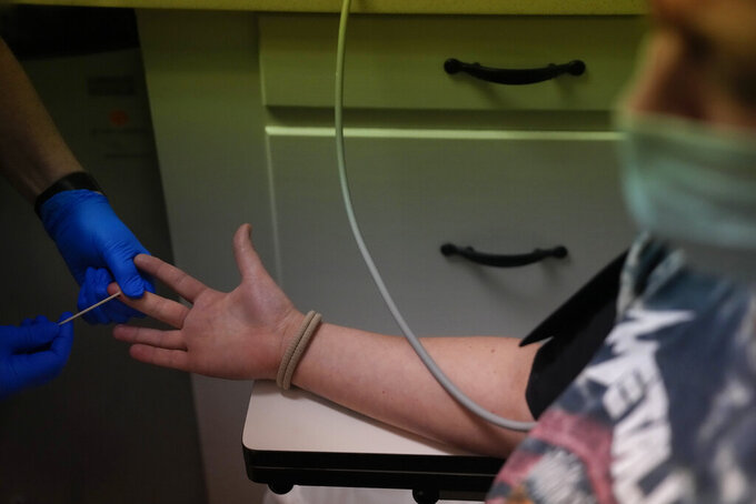 A 25-year-old from Texarkana, whose husband and nursing toddler waited for her outside in their car, has blood drawn ahead of being given pills and guidance for a medical abortion, Saturday, Oct. 9, 2021, at Hope Medical Group for Women in Shreveport, La. The nation's most restrictive abortion law is driving many women from Texas to seek services in neighboring states. The woman said she was already five weeks along before she realized she was pregnant, and she knew it would be impossible to schedule the required two visits at a Texas clinic. (AP Photo/Rebecca Blackwell)
