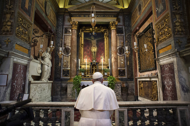 Pope Francis prays in S. Marcello al Corso church, in front of a miraculous crucifix that in 1552 was carried in a procession around Rome to stop the great plague, Sunday, March 15, 2020. For most people, the new coronavirus causes only mild or moderate symptoms. For some, it can cause more severe illness, especially in older adults and people with existing health problems. (Vatican News via AP)