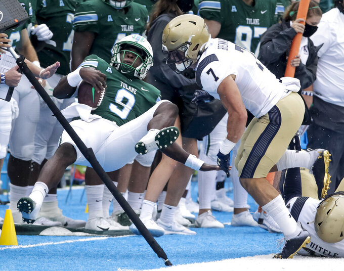 Tulane quarterback Keon Howard (9) knocked out of bounds by Navy linebacker Kevin Brennan (7), drawing a roughing penalty, during the first half an NCAA college football game, Saturday, Sept. 19, 2020, in New Orleans. (Scott Threlkeld/The Times-Picayune/The New Orleans Advocate)
