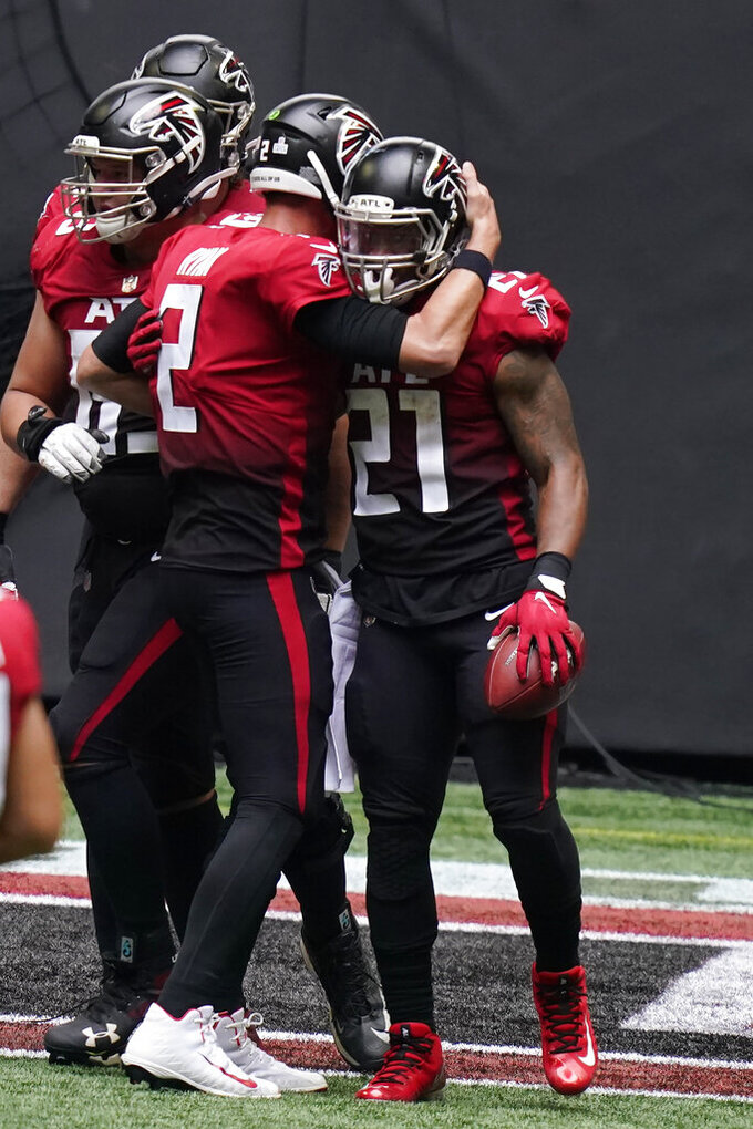 Atlanta Falcons quarterback Matt Ryan (2) congratulates Atlanta Falcons running back Todd Gurley after Gurley scored a touchdown against the Detroit Lions during the first half of an NFL football game, Sunday, Oct. 25, 2020, in Atlanta. (AP Photo/Brynn Anderson)