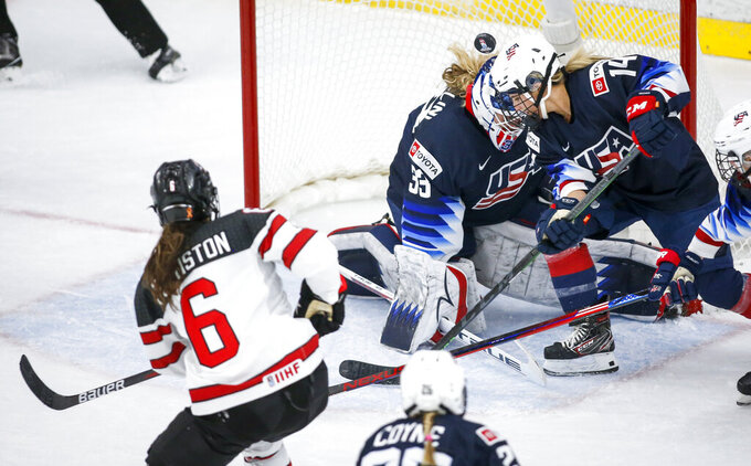U.S. goalie Alex Cavallini, center, and teammate Brianna Decker lose track of the puck as Canada's Rebecca Johnston looks for a rebound during the first period of an IIHF women's world hockey championships game Thursday, Aug. 26, 2021, in Calgary, Alberta. (Jeff McIntosh/The Canadian Press via AP)