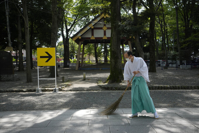 Workers sweep the area along the men's cycling road race prior to its start, outside the Okunitama Shrine, at the 2020 Summer Olympics, Saturday, July 24, 2021, in Fuchu, Japan. (AP Photo/Christophe Ena)