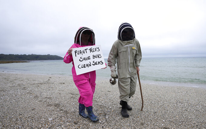 Climate activists Delores and Leroy Tycklemore wear bee keeping suits as they demonstrate as part of Fridays for Future at Gyllyngvase Beach in Falmouth, Cornwall, England, Friday, June 11, 2021. Leaders of the G7 begin their first of three days of meetings on Friday in Carbis Bay, in which they will discuss COVID-19, climate, foreign policy and the economy. (AP Photo/Kirsty Wigglesworth)