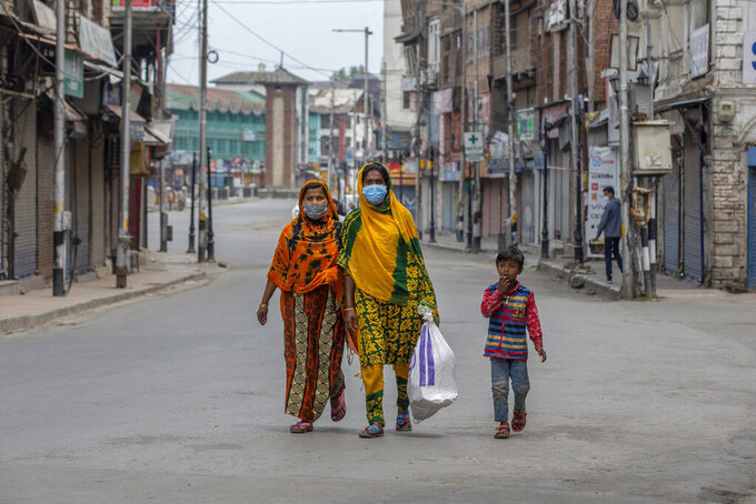 Indian women walk through a deserted road during a lockdown to curb the spread of coronavirus after collecting food item distributed as relief in Srinagar, Indian controlled Kashmir, Wednesday, May 5, 2021. (AP Photo/ Dar Yasin)