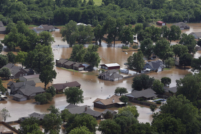 FILE - In this May 23, 2019, file photo, homes are inundated with flood waters from the Arkansas River in Sand Springs, Okla. Oklahoma Gov. Kevin Stitt says the Federal Emergency Management Agency has approved disaster assistance for 41 Oklahoma counties as a result of spring flooding and severe weather in the state. (Tom Gilbert/Tulsa World via AP)