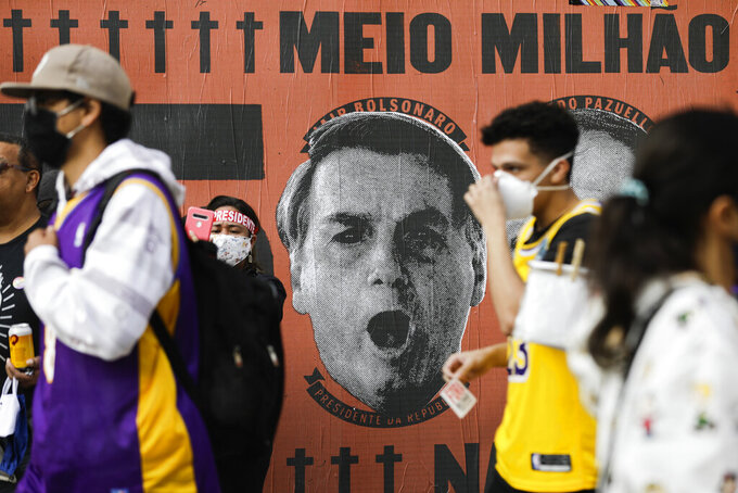 FILE - In this June 19, 2021 file photo, demonstrators walk past a mural depicting the face of Brazilian President Jair Bolsonaro during a demonstration against Bolsonaro's handling of the coronavirus pandemic and economic policies protesters say harm the interests of the poor and working-class on Paulista Avenue in Sao Paulo, Brazil. In the first quarter of 2021, Brazil saw its highest unemploymentand economic inequality in at least nine years, with the cost of living surging and tent cities and shantytowns emerging. (AP Photo/Marcelo Chello, File)