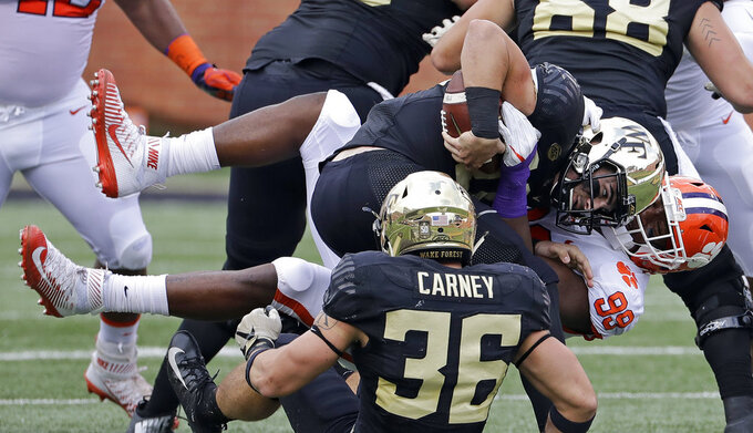 Clemson's Clelin Ferrell (99) sacks Wake Forest's Sam Hartman, center, during the first half of an NCAA college football game in Charlotte, N.C., Saturday, Oct. 6, 2018. (AP Photo/Chuck Burton)