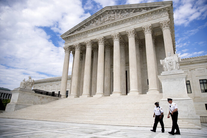FILE - In this May 14, 2020, file photo security officers walk in front of the Supreme Court in Washington. (AP Photo/Andrew Harnik, File)