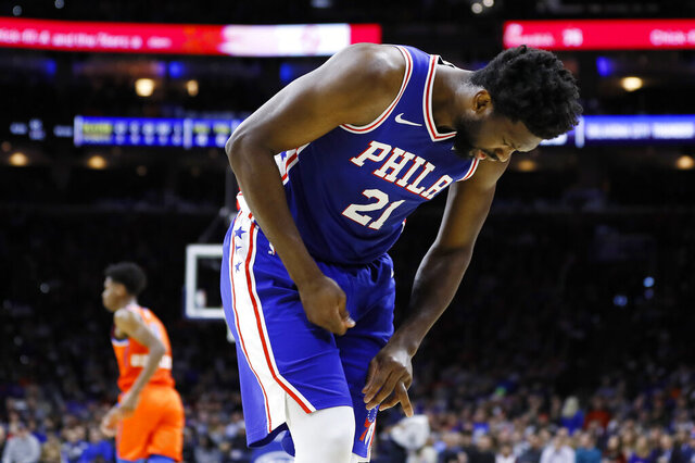 In this photo taken Jan. 6, 2020, Joel Embiid looks at his injured finger during an NBA basketball game against the Oklahoma City Thunder in Philadelphia. Embiid injured the radial collateral ligament in the ring finger in the first half Monday night against Oklahoma City. (AP Photo/Matt Slocum)