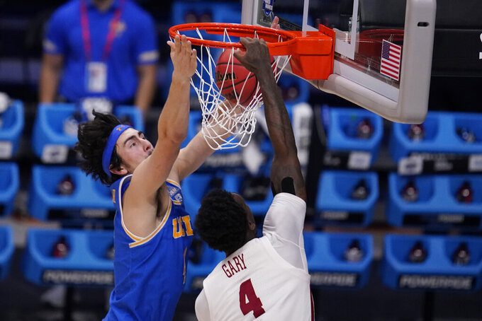 Alabama forward Juwan Gary (4) dunks on UCLA guard Jaime Jaquez Jr. (4) in the first half of a Sweet 16 game in the NCAA men's college basketball tournament at Hinkle Fieldhouse in Indianapolis, Sunday, March 28, 2021. (AP Photo/Michael Conroy)