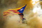 A man holding an independence flag is seen through the smoke thrown by demonstrators during the Catalan National Day in Barcelona, Spain, Wednesday, Sept. 11, 2019. The traditional September 11, called