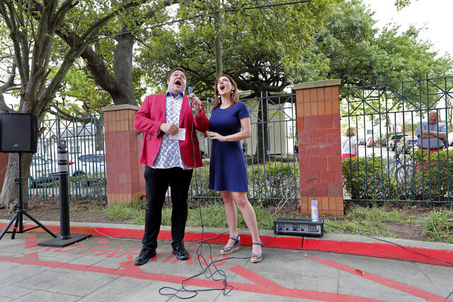 Opera singers Irini Hymel and Bryan Hymel sing to quarantined residents of Lambeth House, where a cluster of the coronavirus has formed, in New Orleans, Friday, March 20, 2020. Several resident have died of the virus. (AP Photo/Gerald Herbert)