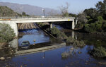 A car sits in flooded water on Highway 101 in Montecito, Calif., Thursday, Jan. 11, 2018. Rescue workers slogged through knee-deep ooze and used long poles to probe for bodies Thursday as the search dragged on for victims of Tuesday's storm after mudslides slammed this wealthy coastal town. (AP Photo/Marcio Jose Sanchez)