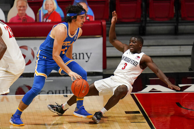 UCLA guard Jaime Jaquez Jr., left, is called for charging on San Diego State guard Terrell Gomez (3) during the first half of an NCAA college basketball game Wednesday, Nov. 25, 2020, in San Diego. (AP Photo/Gregory Bull)