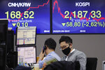 A currency trader wearing a mask watches a calendar at the foreign exchange dealing room of the KEB Hana Bank headquarters in Seoul, South Korea, Tuesday, Jan. 28, 2020. Asian shares continued to fall Tuesday, dragged down by worries about an outbreak of a new virus in China that threatens global economic growth. (AP Photo/Ahn Young-joon)