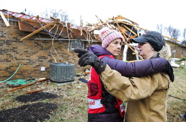 Cathie Morris, right, tells Red Cross volunteer Laurie Howell on Tuesday, December 17, 2019 that her sister was killed by one of the April 2011 tornadoes, not far from what they're standing, in front of Morris' house, damaged by the Monday, December 16, 2019 storms off Neely Hill Loop in Limestone County, Ala.  (Jeronimo Nisa/The Decatur Daily via AP)