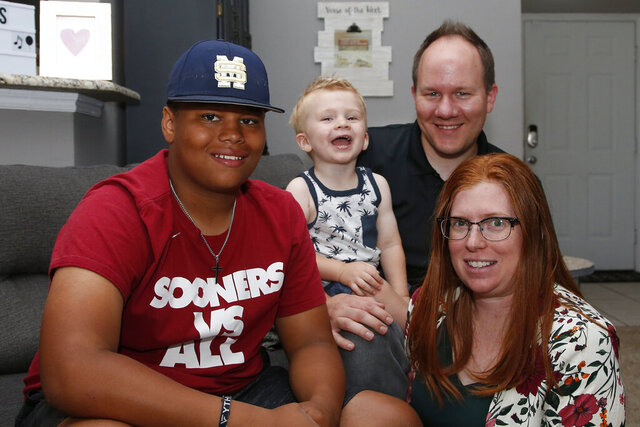 The Dunn family is pictured in their home Friday, June 12, 2020, in Oklahoma City. From left are Izzy Simons, Cooper Dunn, Josh Dunn and Sarah Dunn. Sarah Dunn, who grew up in rural Kansas, has learned much about race since she and her husband, Josh, took custody of Izzy six years ago. (AP Photo/Sue Ogrocki)