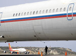 A Chinese airplane is framed by the fuselage of a Russian airplane at the Simon Bolivar International Airport in Maiquetia, near Caracas, Venezuela, Friday, March 29, 2019. Aid was unloaded from the Chinese plane in what Venezuelan officials said would be the first delivery of many from China, an ally of the government of President Nicolas Maduro. (AP Photo/Natacha Pisarenko)