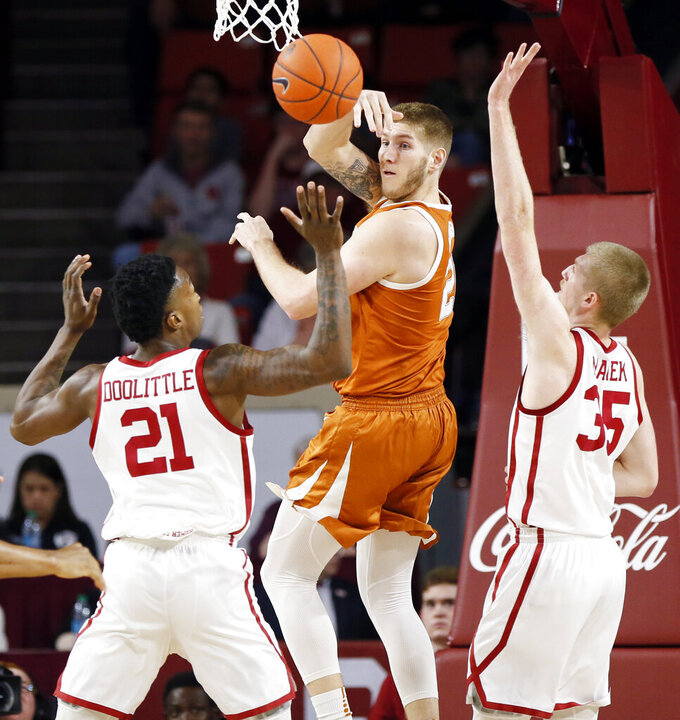 Texas' Dylan Osetkowski (21) passes between Oklahoma's Kristian Doolittle (21) and Brady Manek (35) during the first half of an NCAA college basketball game in Norman, Okla., Saturday, Feb. 23, 2019. Oklahoma won 69-67. (Nate Billings/The Oklahoman via AP)