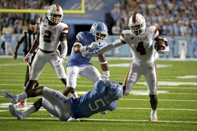 Miami's Jeff Thomas (4) tries to get away from a tackle by North Carolina's Patrice Rene (5) and Myles Wolfolk (11) while K.J. Osborn (2) watches during the second quarter of an NCAA college football game in Chapel Hill, N.C., Saturday, Sept. 7, 2019. (AP Photo/Chris Seward)