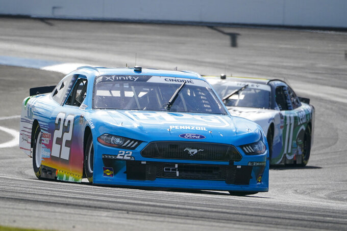 Austin Cindric (22) leads Justin Haley (11) into the second turn during the NASCAR Xfinity Series auto race at Indianapolis Motor Speedway in Indianapolis, Saturday, Aug. 14, 2021. (AP Photo/Michael Conroy)