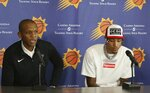Phoenix Suns general manager James Jones, left, talks about he re-signing of Kelly Oubre Jr., right, to the Suns NBA basketball team Tuesday, July 16, 2019, in Phoenix. (AP Photo/Ross D. Franklin)