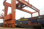 In this July 25, 2019, photo, a crane lifts a shipping container from a truck next to a cargo train bound for Europe at a train station in Dalian in northeastern China's Liaoning Province. Authorities in China's rust-belt region are looking for support for its revival from Beijing's multibillion-dollar initiative to build ports, railways and other projects abroad. (AP Photo/Olivia Zhang)