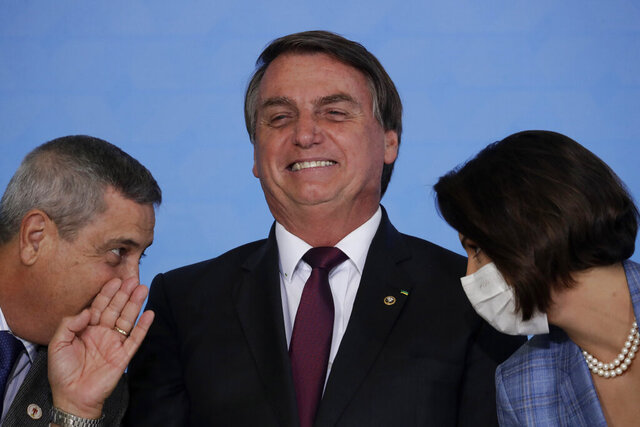 Brazil's President Jair Bolsonaro, center, smiles while flanked by Chief of Staff Braga Netto and first lady Michelle Bolsonaro, during a ceremony on digital social savings and the payment of aid to families amid the COVID-19 pandemic, in Brasilia, Brazil, Wednesday, Nov. 4, 2020. (AP Photo/Eraldo Peres)