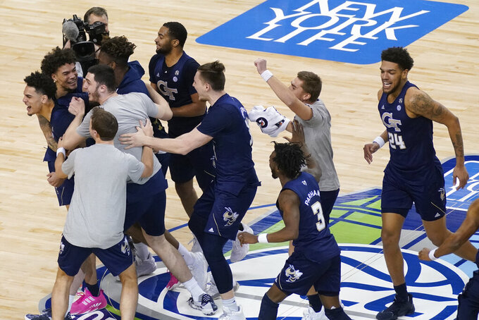 Georgia Tech basketball players celebrate their 80-75 win over Florida State in the Championship game of the Atlantic Coast Conference tournament in Greensboro, N.C., Saturday, March 13, 2021. (AP Photo/Gerry Broome)