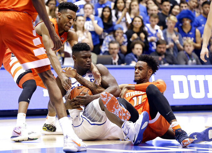 Duke's Zion Williamson holds the ball while Syracuse's Tyus Battle, left, and Oshae Brissett (11) reach in during overtime in an NCAA college basketball game in Durham, N.C., Monday, Jan. 14, 2019. Syracuse won 95-91. (AP Photo/Gerry Broome)