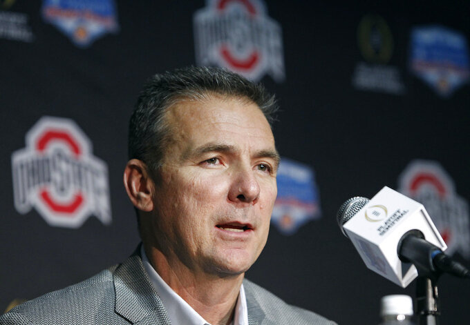 FILE - In this Dec. 31, 2016, file photo, Ohio State head coach Urban Meyer speaks to the media after arriving with his team at Phoenix Sky Harbor Airport, in Phoenix. Ohio State says Urban Meyer will retire after the Rose Bowl and assistant Ryan Day will be the next head coach. After seven years and a national championship at Ohio State, the 54-year-old Meyer will formally announce his departure Tuesday, Dec. 4, 2018, at a news conference. (AP Photo/Ralph Freso, File)