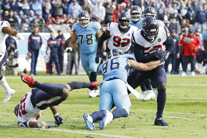 Houston Texans outside linebacker Whitney Mercilus, right, intercepts a pass intended for Tennessee Titans tight end Anthony Firkser (86) in the first half of an NFL football game Sunday, Dec. 15, 2019, in Nashville, Tenn. Mercilus returned the ball 86 yards. (AP Photo/James Kenney)