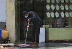 An Indian shopkeeper wearing a  face mask cleans the floor in Hyderabad, India, Tuesday, July 7, 2020. India has overtaken Russia to become the third worst-affected nation by the coronavirus pandemic. (AP Photo/Mahesh Kumar A.)
