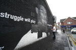 """Ed Wellard, from Withington, tapes bin liners across offensive wording on the mural of Manchester United striker and England player Marcus Rashford on the wall of the Coffee House Cafe on Copson Street, which appeared vandalised the morning after the England soccer team lost the Euro 2021 final against Italy, in Withington, Manchester, England, Monday,  July 12, 2021.  British Prime Minister Boris Johnson has condemned the racist abuse directed at three Black England players who missed their penalties in the team's shootout loss to Italy in the final of the European Championship on Sunday. Johnson tweeted that """"those responsible for this appalling abuse should be ashamed of themselves."""" Marcus Rashford's penalty hit the post and spots kicks from Bukayo Saka and Jadon Sancho were saved by Italy's goalkeeper. (Peter Byrne/PA via AP)"""