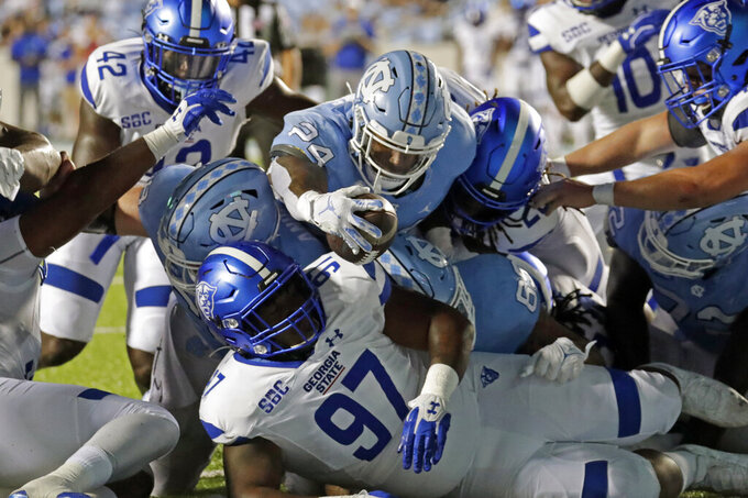 North Carolina running back British Brooks (24) shoves the ball over Georgia State defensive lineman Akeem Smith (97) to score a touchdown during the second half of an NCAA college football game in Chapel Hill, N.C., Saturday, Sept. 11, 2021. (AP Photo/Chris Seward)