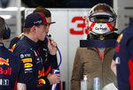 Red Bull driver Max Verstappen of the Netherlands, second left, drinks as he waits in his garage during the Formula One pre-season testing session at the Barcelona Catalunya racetrack in Montmelo, outside Barcelona, Spain, Friday, Feb. 28, 2020. (AP Photo/Joan Monfort)