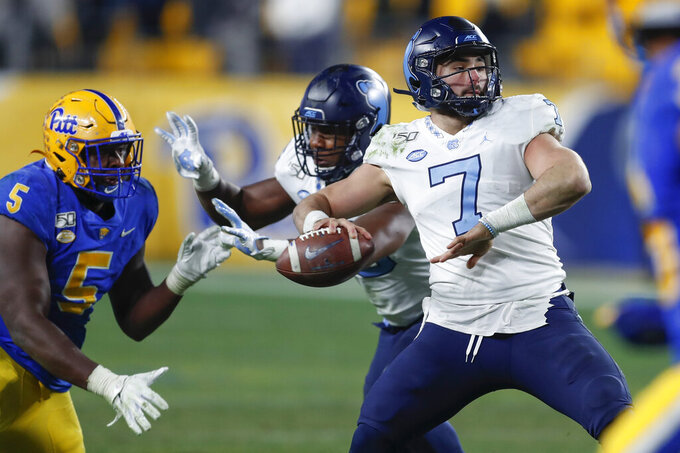 North Carolina quarterback Sam Howell (7) looks to the end zone on fourth down as Pittsburgh defensive lineman Deslin Alexandre (5) pressures during the last play of overtime in an NCAA college football game Thursday, Nov. 13, 2019, in Pittsburgh. The pass was incomplete and Pittsburgh won 34-27. (AP Photo/Keith Srakocic)