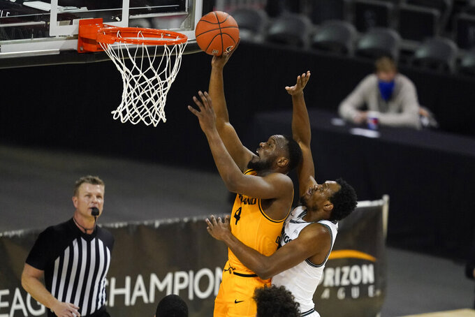 Oakland's Daniel Oladapo (4) puts up a shot against Cleveland State's Deante Johnson (35) during the first half of an NCAA college basketball game in the men's Horizon League conference tournament championship game, Tuesday, March 9, 2021, in Indianapolis. (AP Photo/Darron Cummings)