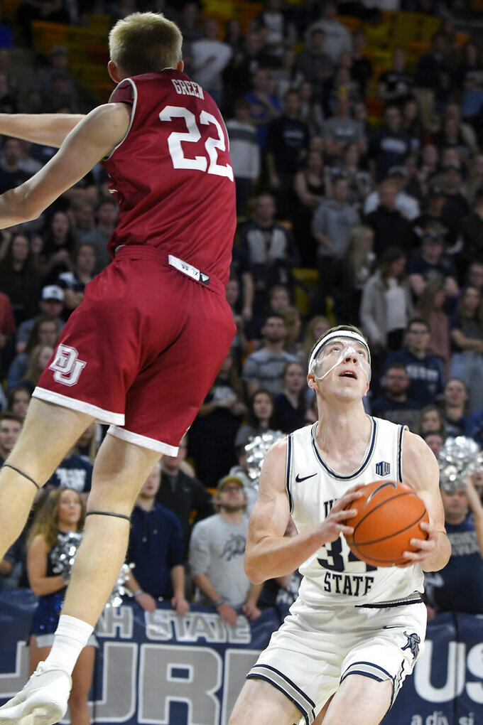 Utah State forward Justin Bean (34) looks to shoot the ball as Denver forward Tristan Green (22) defends during the first half of an NCAA college basketball game Tuesday, Nov. 12, 2019, in Logan, Utah. (AP Photo/Eli Lucero)