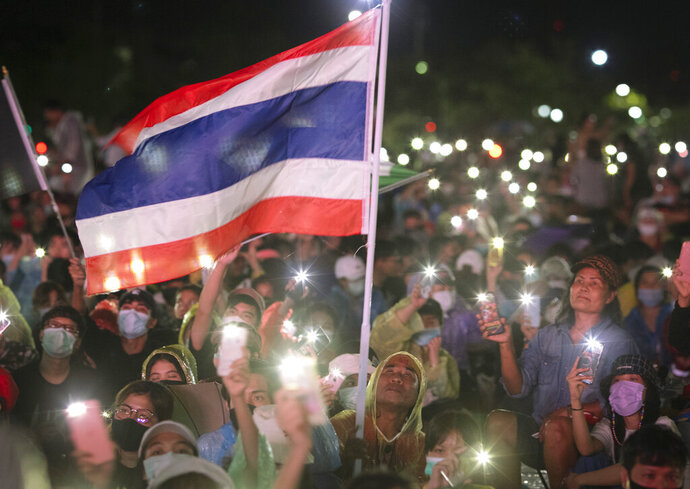 Pro-democracy protesters wave a flag and hold up lights during a protest at Sanam Luang in Bangkok, Thailand, Saturday, Sept. 19, 2020. Thousands of demonstrators turned out Saturday for a rally to support the student-led protest movement's demands for new elections and reform of the monarchy. (AP Photo/Wason Wanichakorn)