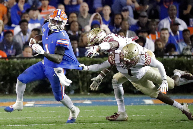 Florida wide receiver Kadarius Toney, left, tries to escape the grasp of Florida State defensive back Levonta Taylor, back right, during the first half of an NCAA college football game Saturday, Nov. 30, 2019, in Gainesville, Fla. (AP Photo/John Raoux)