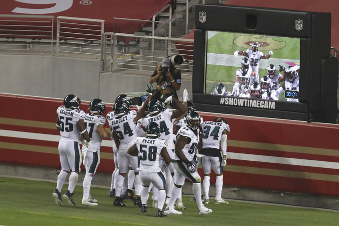 Philadelphia Eagles players celebrate in front of a video screen after Alex Singleton returned an interception for a touchdown during the second half of an NFL football game against the San Francisco 49ers in Santa Clara, Calif., Sunday, Oct. 4, 2020. (AP Photo/Jed Jacobsohn)